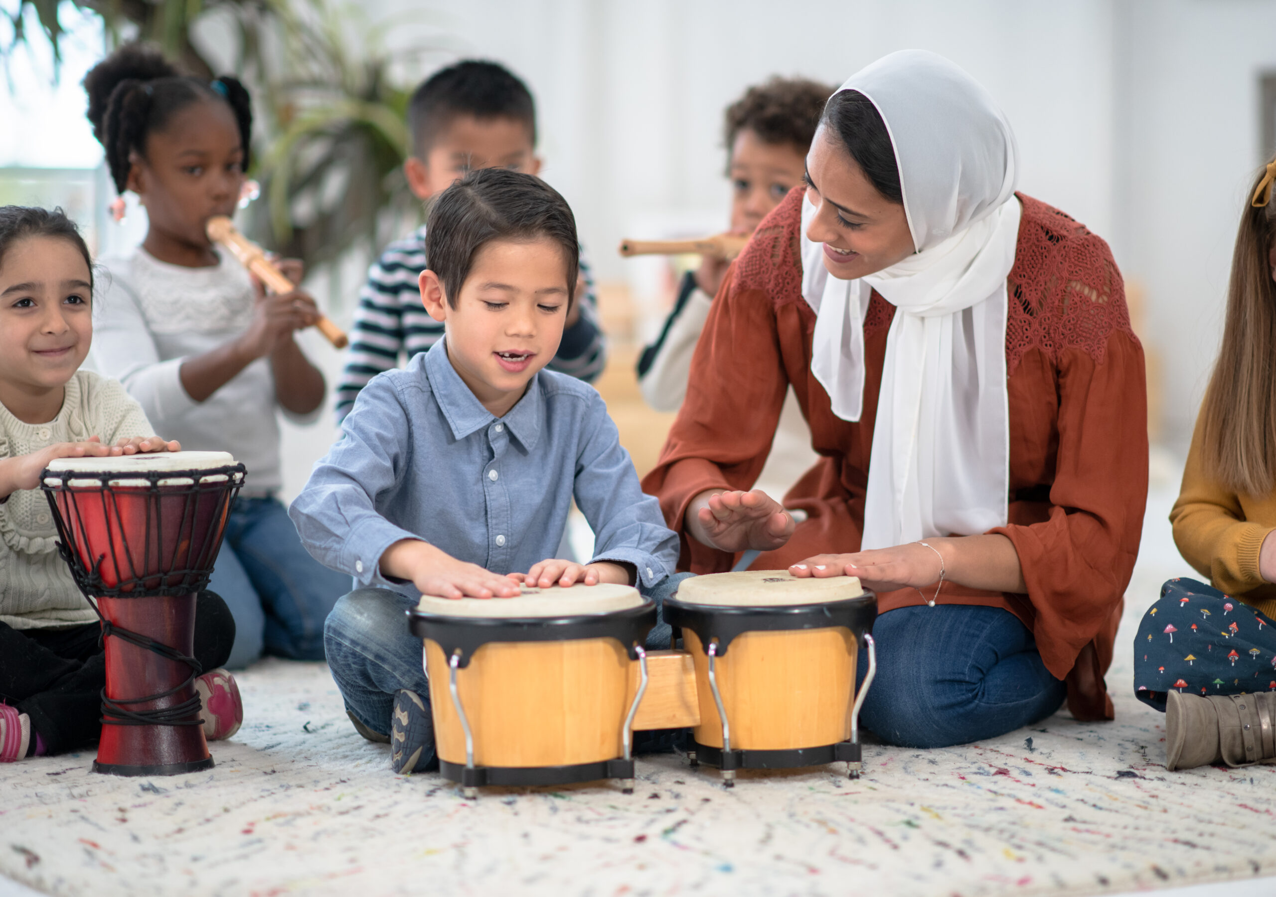 An adorable little Asian boy plays the bongo drums in his classroom while his teacher sits next to him.